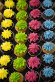 Vertical four rows of colorfully frosted cupcakes Stock Photos