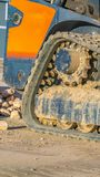 Vertical frame Close up of the dirty rubber track of a heavy duty construction machinery. In front of vehicle is a pile of rocks and house viewed on a sunny stock image