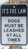 Vertical frame Close up of a Dog Leash sign on a wooden post against a snowy landscape. The signage reads It`s The Law, Dogs Must Be Leashed At All Times stock photos