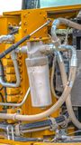 Vertical frame Close up of the engine of a yellow heavy duty construction machinery. The motor and tubes energizes vehicle and enables it to operate royalty free stock image