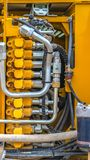 Vertical frame Details of the engine which gives power to a construction machinery. Sevral pipes and tubes are attached to the motor of the yellow heavy duty stock photography