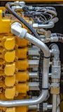 Vertical frame Details of the engine of a yellow heavy duty construction vehicle. Several tubes and pipes are attached to the motor which gives power to the stock photography