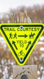 Vertical frame Inverted triangle Trail Courtesy Yield To sign with graphics and arrows. Trees on a snow covered landscape in winter can be seen in the blurred royalty free stock photo
