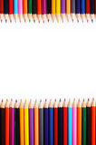 Vertical frame of a large number of colored pencils on white bac Royalty Free Stock Images
