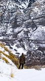 Vertical frame Man with a view of a majestic mountain covered with powdery snow in winter. The man is standing alone at the bottom of a frosted mountain slope stock images