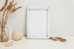 Vertical frame mockup with wild rye bouquet in glass vase near white wall. Empty frame mock up for presentation design. Template framing for modern art. Hygge royalty free stock photography