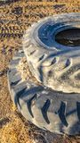 Vertical frame Old and dirty rubber tires stacked on top of each other viewed on a sunny day. Tire tracks are imprinted on the dry soil near the wheels stock photography