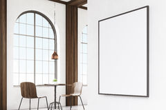 Vertical framed poster on a cafe wall, corner. Corner of a cafe with a vertical framed poster hanging on a gray wall. Wooden tables and chairs. 3d rendering Royalty Free Stock Photo