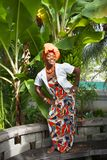 The vertical full body of a joyful African American woman wearing a bright colorful national dress poses in the garden stock photo