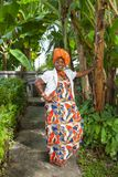 The vertical full body of a joyful African American woman wearing a bright colorful national dress poses royalty free stock photo