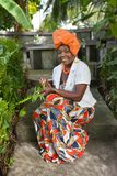 The vertical full body of a joyful African American woman wearing a bright colorful national dress sits in the garden. Against the background of banana trees stock image