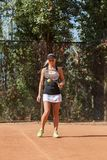 Vertical full body portrait of blonde female tennis player with ball on court outdoor. Full body image of caucasian blonde female tennis player with ball on Royalty Free Stock Photo