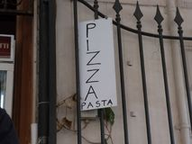Pizza Pasta signage in Rome, Italy. Vertical handwritten placard with the Italian text `Pizza Pasta` outside a door stock image