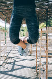Vertical image of an athletic young woman doing pull-ups outdoor. S in the morning, close-up. Female legs in blue sneakers stock photo