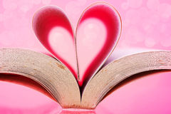 Vertical Image of book pages into a heart shape of pink background Stock Photo
