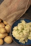 Mash potato topped with chives and a sack of whole potatoes royalty free stock image