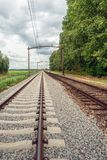 Rusty train tracks with overhead lines in the Netherlands. Vertical image of a Dutch landscape with rusty, seemingly endless long train tracks with overhead stock photography