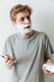 Vertical image of Incomprehensible man in shaving foam Royalty Free Stock Images