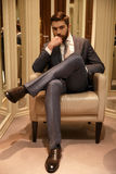 Vertical image of man sitting on armchair. Vertical image of a man in suit sitting on armchair in a shop and looking at camera royalty free stock photos