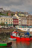 Vertical image of the old iconic traditional waterfront shophouses with red vessel at Cobh, Republic of Ireland royalty free stock photo