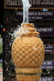 Vertical image of pineapple fountain with water spilling from top and over sides Royalty Free Stock Photography