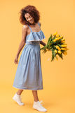Vertical image of pleased african woman holding bouquet flowers Stock Images