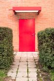Vertical image. Red door surrounded by orange brick wall. royalty free stock image