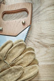Vertical image of safety gloves stainless hacksaw on wooden boar Stock Photo