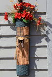 Vertical image of silk flowers in hancrafted basket, attached to outside wall of home Royalty Free Stock Photography