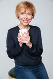 Vertical image of Smiling elderly woman holding cup  tea Stock Photo
