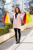 Vertical image of Smiling woman holding packages. Vertical image of Smiling woman in coat holding packages and standing on the street royalty free stock photos