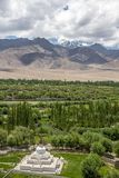 Stok Kangri and fertile Indus valley from Shey Monastery, Leh. Vertical image with views of a white stupa near Shey Monastery, the trees and vegetation of the stock image