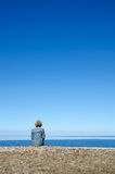 Vertical image of woman sitting by a coast with clear blue and c Royalty Free Stock Images