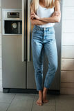 Vertical image of woman standing near the fridge. Vertical image of a woman with crossed arms standing on kitchen near the fridge. Cropped picture royalty free stock image