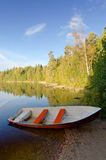 Vertical lake landscape with red rowboat Stock Photo