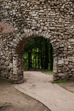 Vertical location of an arch and a stone wall, paths and forests in the background Royalty Free Stock Image