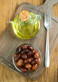 Vertical making bowl of olives and oil on wood Royalty Free Stock Photos