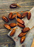 Vertical making of branch of date fruits on wood Royalty Free Stock Photos