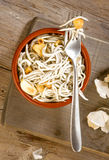Vertical making mud pie plate with fried baby eels with garlic Stock Photography