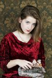 Vertical medium shot of exquisite pale blue-eyed young woman wearing red velvet dress stock image