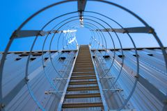 Vertical metal staircase to the roof of the hangar. Staircase surrounded by a protective frame.  stock photography