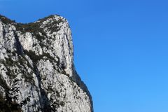 Vertical mountain cliff face against clear blue sky. In summer royalty free stock photos