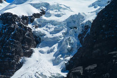 Vertical mountain glacier. Blue ice among dark rocks in the high mountains Royalty Free Stock Photos