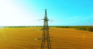 Vertical movement flight near high voltage electricity tower and power lines at green and yellow field stock footage