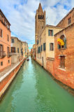 Small canal and typical buildings in Venice, Italy. Royalty Free Stock Photo