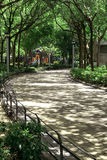 Vertical outdoor playground, footpath and tree in public park Stock Photos