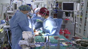 Vertical pan of operating room and surgical team (1 of 2) stock video