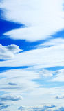 Vertical panaramic cloudscape. Thin light layered clouds that spread in front of heavy weather-changing clouds Stock Photo