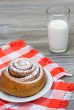Vertical photo of appetite cinnamon roll on chechered tablecloth. And glass of milk Royalty Free Stock Image