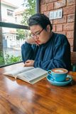 Vertical photo of Asian girl reading book and drinking coffee royalty free stock image